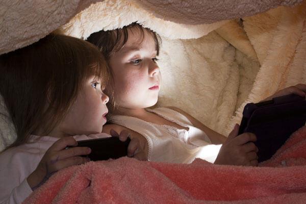 Niños con tablet por la noche